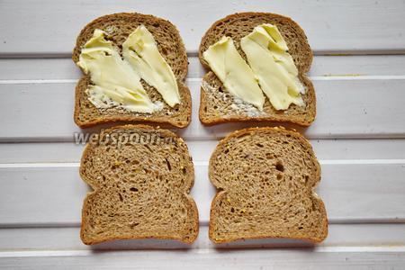 Половинки хлеба намазать мягким сливочным маслом. Поставить разогреваться сэндвичницу.