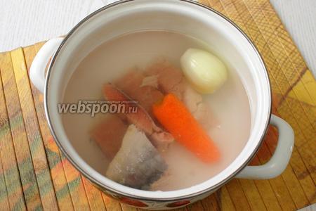 В воду закладываем нарезанное филе горбуши, очищенные морковь и лук.