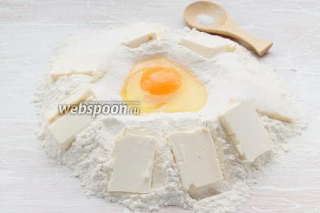Высыпаем щепотку соли, 65 г сахара в центр вбиваем яйцо, по краям раскладываем пластинки твёрдого (холодного) масла.