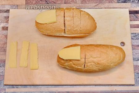 Булочки нужно брать продолговатые, разрезаем их на 2 половинки. Из сыра вырезаем необходимые части, ногти и промежутки для сгибов. Укладываем сыр на хлеб.