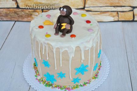 Выложить на торт конфеты, снежинки из мастики отлично приклеятся к кремовой поверхности. Присыпать низ торта кондитерской посыпкой. Посадить рядом с конфетами обезьянку. О! Не забудем дать ей в руки бананы. Их тоже сделаем из мастики.