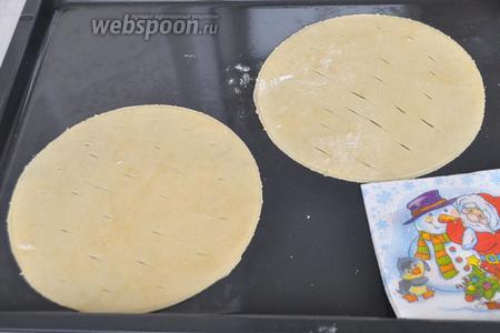 Раскатываем очень тонко. Обрезаем по форме. В этот раз у меня торт небольшой и я использую круг диаметром 20 см. На лист помещается 2 коржа. Не забудем проколоть коржи вилкой или ножом, чтобы не вздувались.