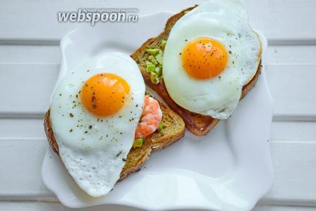 На сковороде, где жарился хлеб обжарим по отдельности 2 яйца, чуть посолив и поперчив сверху. Как только яйца будут готовы, — выложим их верхним слоем на тосты. Завтрак готов, приятного аппетита!
