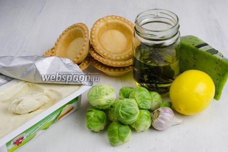 Чтобы приготовить закуску, нужно взять готовые тарталетки, брюссельскую капусту, масло, чеснок, лимон, сыр сливочный с зеленью и твёрдый сыр с базиликом.
