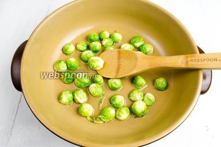 На разогретую сковороду с оливковым маслом выложить капусту, хорошо перемешать. Жарить минуты 2.