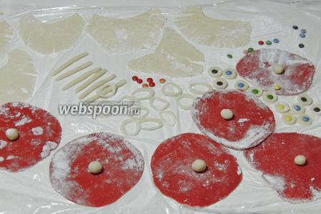 Раскатываем между плёнками красный марципан в круги — 6 штук. Из оставшегося белого марципана лепим помпоны на шапки. Докомплектовываем все марципановые части. Вставляем драже Смарти в кружки для глаз, это будут зрачки.