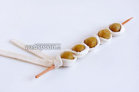 Перекрещивая полоски теста между собой, обматываем  его вокруг оливок. Остаток теста убираем. Из них потом можно приготовить солёные палочки.