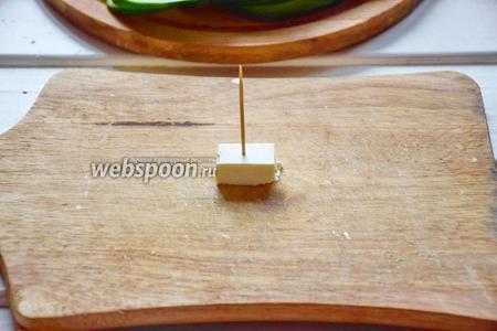 Сыр Фета мы также нарежем квадратами. Постарайтесь сделать их ровными и устойчивыми, так как это будет стержнем канапе, на котором будет держаться всё остальное! Воткнуть зубочистку в центр сырного квадрата. Следом пойдёт огурец, сложенный пополам!