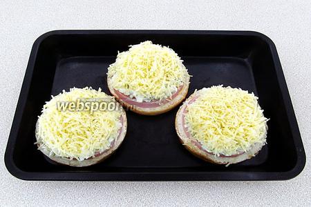Заготовки бутербродов разложить на противне, слегка смазанном маслом, и посыпать сыром.