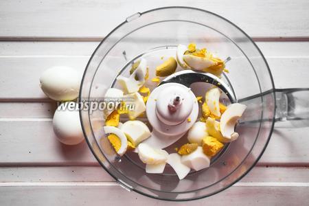 Варёные яйца очистить от скорлупы, нарезать произвольно и сложить в чашу комбайна.