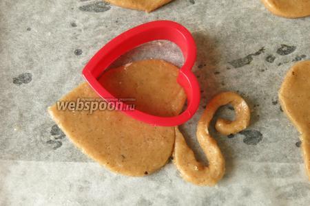 Хвост отгибаем, закручиваем, если хотим, чтобы печенье можно было вешать на чашку, делаем острый угол. С помощью меньшей формы вырезаем половинку сердечка, не дорезая до конца — это мордочка. Можно использовать и большую форму из шага 5, но удобнее управляться маленькой.