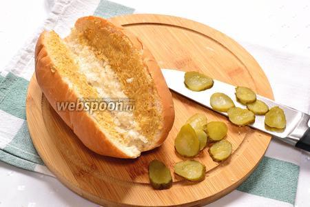 Теперь можем собирать хот-дог. Булочку для хот-дога надрезать посередине. Внутри смазываем горчицей по вкусу. У меня русская горчица (острая), поэтому я её использовала совсем немного. Маринованный огурец нарезать тонкими ломтиками. Огурец разложить по 2 половинкам булочки.