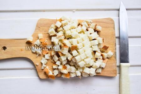 Белый батон нарезаем на маленькие кубики, чем мельче получится, тем удобнее будет кушать!:) Выложить кубики на противень и подсушивать в духовке, разогретой до 160°С, около 10 минут, до золотистого цвета.
