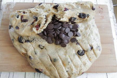 Вынимаем тесто на припорошенное мукой рабочее место. Вмешаем вишни вместе с оставшимся киршем, если остался, и шоколадные пуговки.
