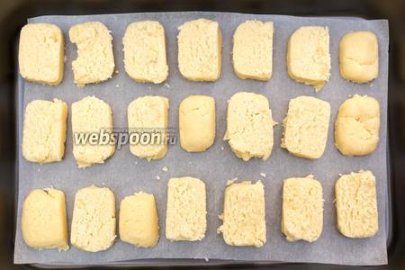 Через 1 час вынимаем тесто. Каждую часть нарежем на кусочки толщиной 1 см. Выкладываем на противень, застеленный пергаментом. Выпекаем в разогретой до 170°С духовке 30 минут.