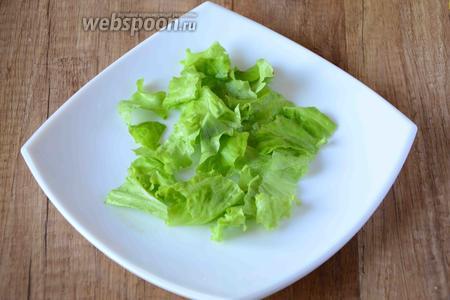 Листья салата порвать руками, разложить в центр сервировочной тарелки.