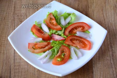 Тонкими полукольцами режем помидор, выкладываем на листья салата. Лук режем тонкими кольцами, выкладываем лук между помидор.