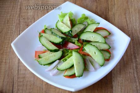 Огурец порезать полукольцами, (наискосок), выложить огурцы на помидоры и лук.