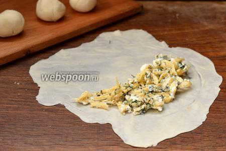 На 1/2 подготовленного теста выложить приблизительно 2 столовых ложки сырной начинки.
