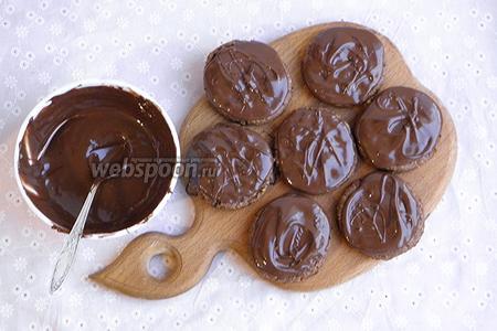Остужаем шоколад в течение 20 минут, постоянно помешивая. За это время шоколад слегка загустеет и это позволит сделать красивые разводы на печенье. Поливаем шоколадом печенье и отправляем в холодильник.