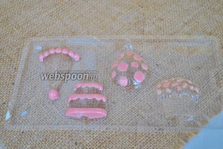 В молде для шоколада с помощью зубочистки или маленькой кисти закрасить шоколадом все те части, которые вы хотите видеть розовыми.