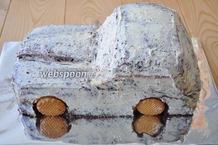 Ложечкой аккуратно вынем бисквит из колёсных арок авто и вставим туда печенье, такое же, которое в колёсах. Это временно, чтобы под давлением коржей торт не деформировался.