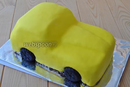 Раскатываем жёлтую мастику и накладываем на авто. Разравниваем утюжком. Вынимаем печенье и ставим настоящие колёса. Обрезаем всё лишнее.