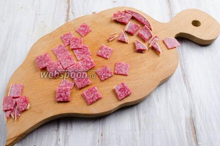 Взять очень острый нож. Нарезку колбасы сложить стопкой 3-4 штуки. Разложить выкройку-квадраты 2х2 см по длине и ширине, чтобы понять, каким размером полоски нарезать. Разрезать колбасу вдоль, а потом поперёк, плотно прижимая её к доске. У вас получатся одинаковые квадратики.