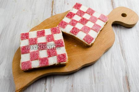 Разложить квадраты из колбасы по куску хлеба, плотно прижимая к слою сыра, в шахматном порядке, как на фото.