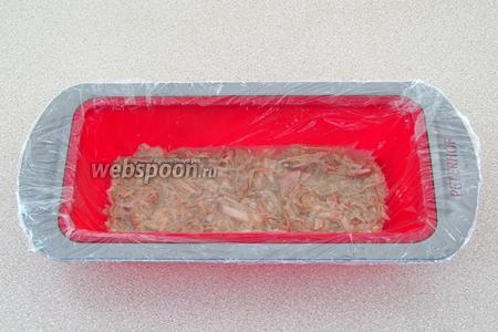 Любую ёмкость прямоугольной формы выложить пищевой плёнкой. Покрыть дно ⅓ мясной массы.