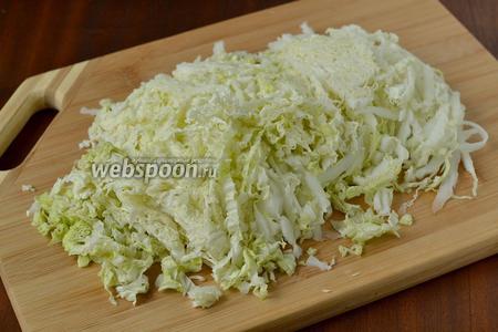 Пекинскую капусту шинкуем тонкой соломкой. Не бойтесь, что получается большой объём. Это из-за гофрированных листочков. После перемешивания с другими ингредиентами объём уменьшится.