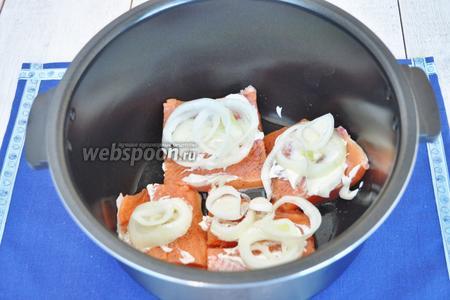 В чашу мультиварки влить подсолнечное масло. Выложить рыбу на кожу. Посолить и поперчить. Смазать майонезом и выложить лук на каждый кусок.