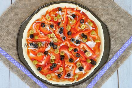 Маслины и оливки порезать на 3 части и равномерно распределить по всей поверхности.
