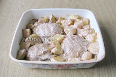 Через 25 минут достаем курицу с картофелем из духовки и смазываем смесью сметаны с кетчупом.  Опять отправляем в духовку на 20-25 минут.