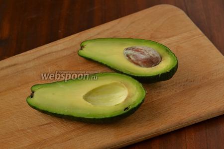 Авокадо разрезаем вдоль, обводя косточку, затем поворачиваем половинки в разные стороны, чтобы разъединить.