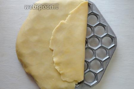 Песочное тесто делим на 2 равные части. Затем раскатываем его в тонкий пласт и укладываем на форму.