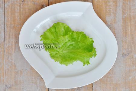 На порционную тарелку уложить пару листиков салата.