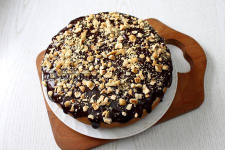 Растопить шоколад на пару, смешать с молоком и полить глазурью кекс. Сразу посыпать измельчёнными орехами.