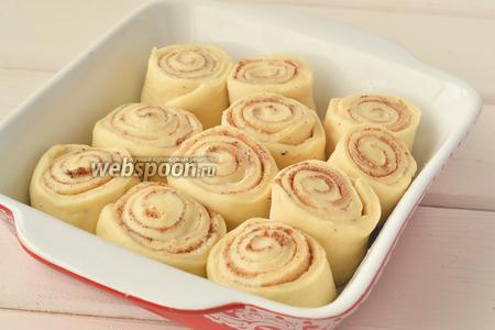 Форму смазать сливочным маслом и выложить булочки, оставляя место для увеличения их в размере.