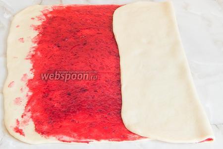 Промазываем тесто подготовленной клюквенной начинкой, оставляя с краёв около 2 сантиметров.