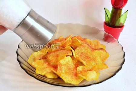 Когда чипсы остынут, сложить их в тарелку, посыпать солью и молотой паприкой по вкусу.