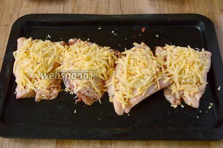 Сыр натереть на крупной тёрке. Хорошо посыпать сыром курицу с ананасами. Запекаем куриные бёдра в разогретой до 200-220°С духовке, около 25-30 минут.