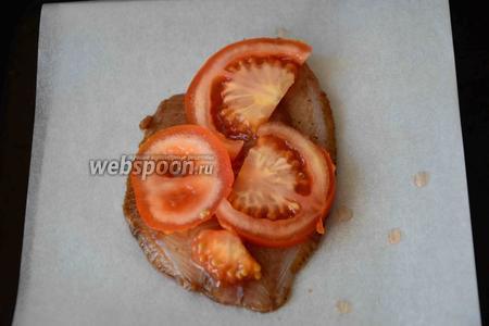 Затем рыбку перекладываем на пергаментную бумагу. Помидоры режем кольцами средней толщины. Выкладываем помидоры на рыбку.