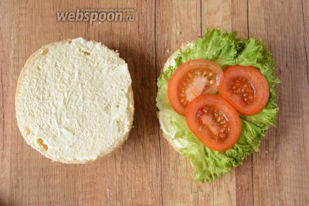 На 1 половинку булочки выкладываем лист салата. Помидор режем тонкими кольцами и выкладываем сверху на салат.