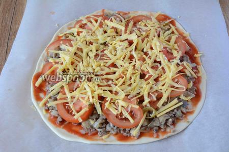 На крупной тёрке натереть сыр, посыпать пиццу сыром. Запекать пиццу в разогретой, до 180-200°С, духовке около 15-20 минут.