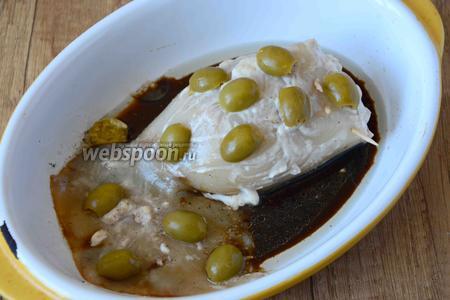 Выливаем в форму остатки соевого соуса. Сверху на кальмар выкладываем разрезанные вдоль оливки.