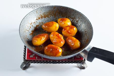 Ввести в растопленный сахар масло, перемешать и обжаривать в этой смеси картошку, пока она не покроется коричневой оболочкой глазури.