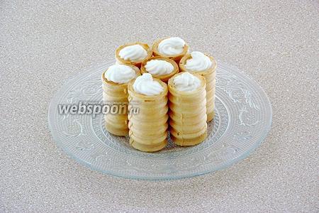 С помощью кондитерского мешка и насадок наполнить вафельные трубочки кремом.