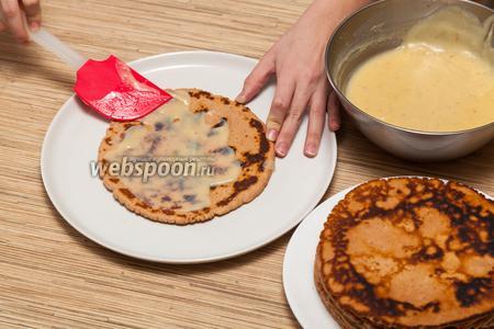 Горячий крем уже можно наносить на коржи, не забывая промазывать бока будущего торта.