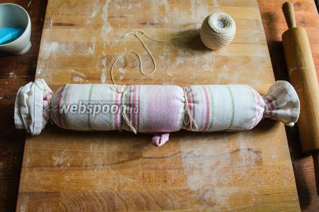 Теперь передвиньте ротоло на край полотенца и заверните его. Свяжите ротоло в 4 местах плотной верёвкой, чтобы он не расползался во время варки.